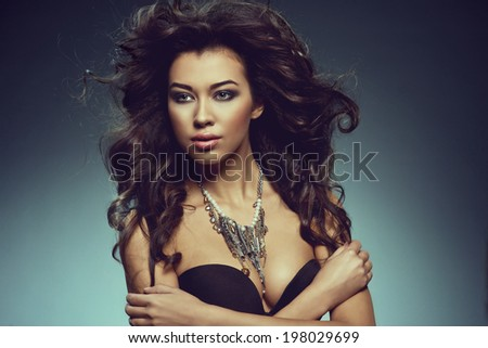 sensual woman posing in black bra with big hair style