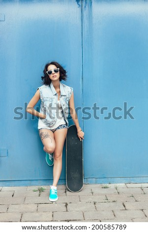 Sensual woman posing with skateboard. Lifestyle outdoor portrait