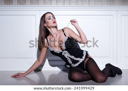 Sensual woman sit at vintage wall with pearls, closed eyes - stock photo