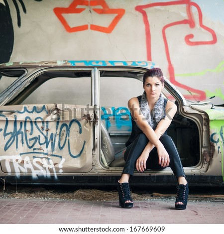 Sensual woman sit in abandoned car.  - stock photo