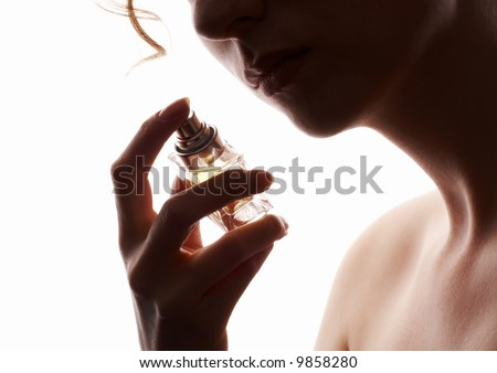 sensual woman smelling perfume, golden perfume bottle