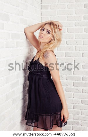 Sensual woman wearing a black dress in front of a wall
