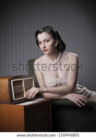 Sensual woman wearing lingerie listening music on old radio - stock photo