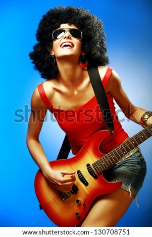 Sensual woman with afro hairstyle playing on the electric guitar against blue background - stock photo