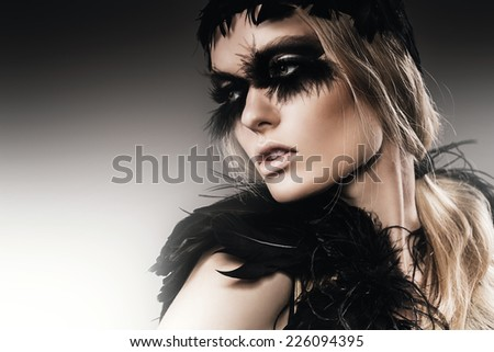 sensual woman with black feathers on eyes - stock photo
