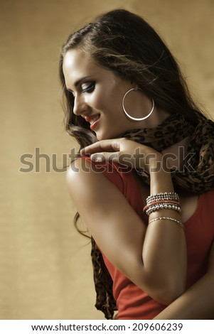 Sensual woman with long brown hair wearing red dress and red lipstick, looking to the side against a warm golden background - stock photo