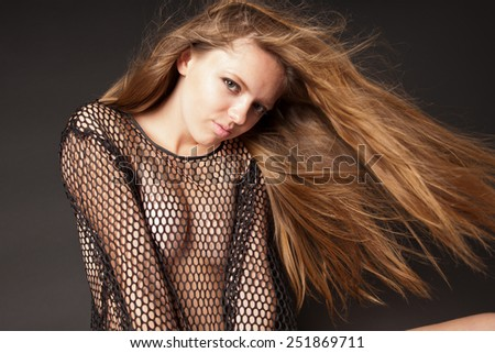 Sensual woman with long hair sitting on black background - stock photo