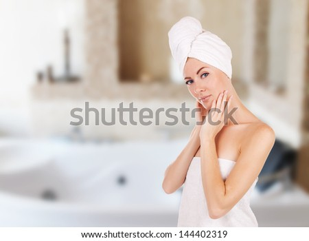 Sensual woman with towel in bathroom with jacuzzi - stock photo