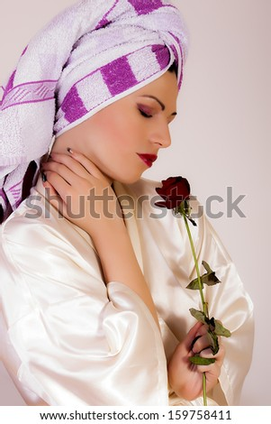 sensual woman with towel on her head holding a flower - stock photo