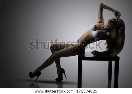 sensual young brunette girl posing with her perfect body on small table wearing sexy white lingerie and heels. Backlight glamour portrait  - stock photo