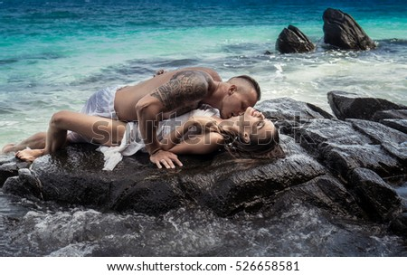 Sensual young couple in white clothes laying on the rock by the sea over sky and tropical island background