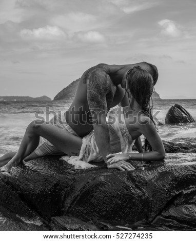 Sensual young couple in white wet clothes kissing while laying on the rock by the sea over sky and tropical island background - black and white photo