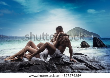 Sensual young couple in white wet clothes sitting on the rock by the sea over blue sky and tropical island background