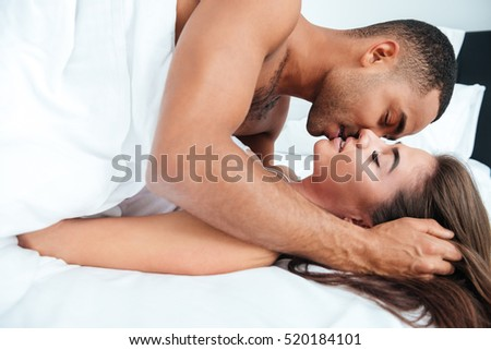 Sensual young couple lying and kissing in bed at home