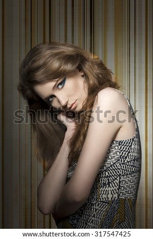 sensual young girl with long natural hair and strong blue make-up in lovely pose with vintage printed dress  - stock photo
