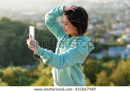 Sensual young japanese woman taking selfie outdoor in park using her phone and smiling