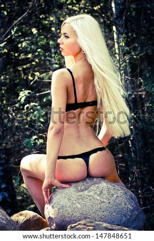 Sensual young lady in lingerie sitting on a stone - stock photo