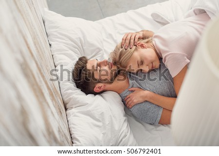 Sensual young man and woman are asleep in bed. They are lying and hugging