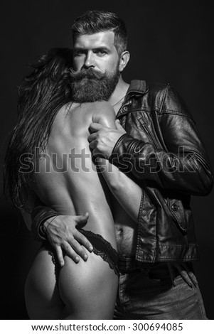 Sensual young pair of bare woman in panties and unshaven man with beard in leather biker jacket and jeans touching and embracing each other on dark background black and white, vertical picture - stock photo