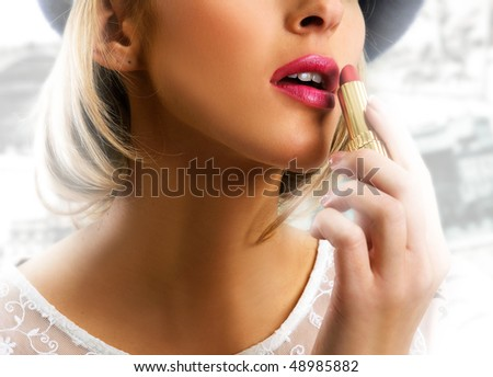 sensual young woman applying cosmetics on her lips - stock photo