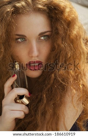 Sensual young woman holding a perfume.Beautiful blonde with bright make up and long wavy hair. vertical shot. - stock photo
