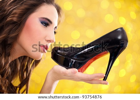 Sensual young woman holding black high heels - stock photo