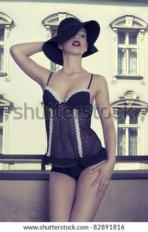 sensual young woman in a fashion shot wearing a black hat and bra  posing outside of the window with old building in background