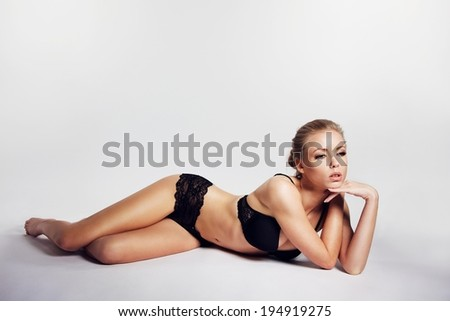 Sensual young woman in lingerie lying over grey background. Pretty young caucasian female model wearing black underwear looking away. Woman posing in lingerie - stock photo