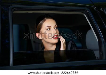 Sensual young woman looking out of a car window with parted lips and a look of anticipation - stock photo