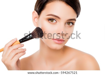 Sensual young woman on isolated white applying blusher on her cheekbones using make-up brush