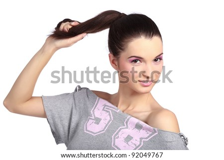 Sensual young woman pulling her hair gently and smiling at the camera. High resolution image taken in studio. Isolated on pure white background with copy space for your ad. - stock photo