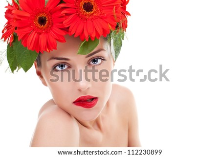 sensual young woman wearing a wreath of gerbera flowers and looking into the camera, biting her red lips, isolated on white