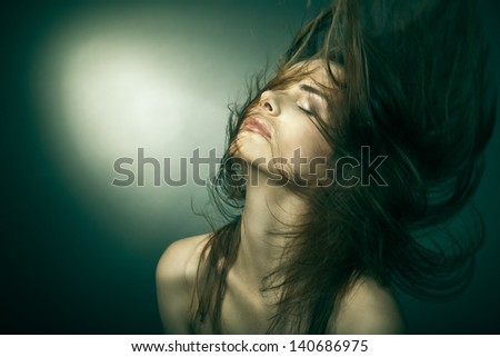 Sensual young woman with beautiful long brown hairs, posing. Studio shot - stock photo