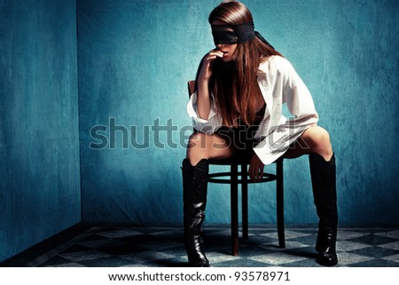 sensual young woman with lace covering eyes sit on chair in shirt and leather boots - stock photo
