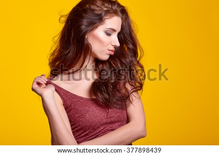 Sensual young woman with natural make-up posing over bright yellow background. Copy space. Cosmetics. Skincare, bodycare. - stock photo