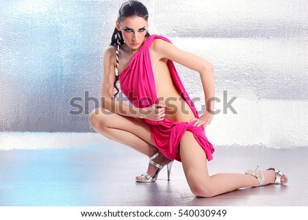 sensual young woman wrapped in pink cloth, against silver background