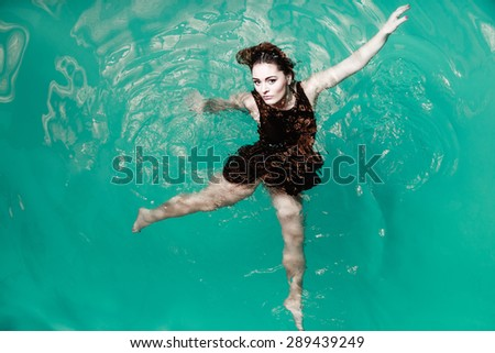 Sensuality and sexuality of women. Sexual posing woman in black dress in water. Indoor.