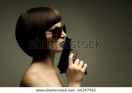 sensuality  beautiful girl, close face , with pistol, on dark background, glamour light - stock photo