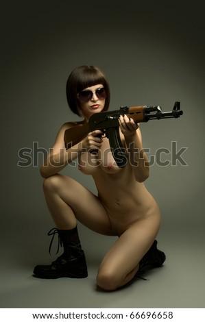 sensuality  beautiful sexy girl nude , on dark background, aiming of submachine, glamour  light - stock photo