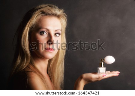 Sensuality concept. Portrait beautiful blonde woman with perfume bottle on black background - stock photo