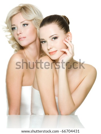 Sensuality faces of two beautiful young adult women are together. Girls posing on white background - stock photo