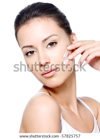 Sensuality in look of young woman applying cream on the face - isolated - stock photo