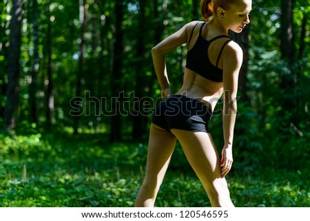 Sensuous slim woman doing fitness in park - stock photo