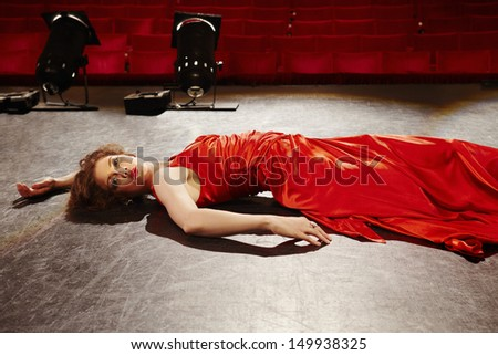 Sensuous young woman in red gown lying on stage floor - stock photo