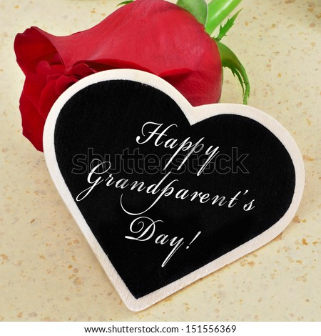 sentence happy grandparents day written with chalk on a heart-shaped blackboard with a red rose in the background - stock photo
