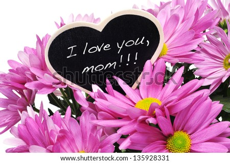 sentence I love you, mom written with chalk on a heart-shaped blackboard on a bouquet of pink chrysanthemums - stock photo