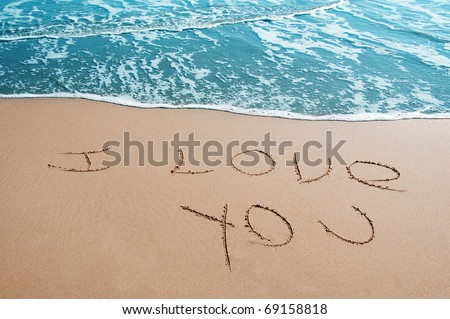 """sentence """"I love you"""" written on the sand of a beach - stock photo"""