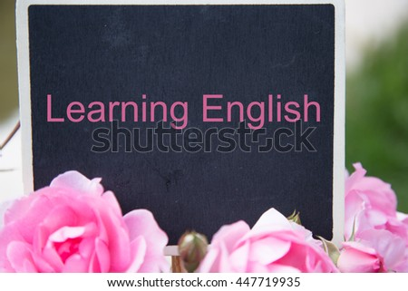 sentence Learning English written with blackboard and bunch of roses with grassland and rice field background - stock photo