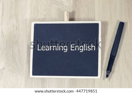 sentence Learning English written with chalk on a blackboard, on a table with pen - stock photo
