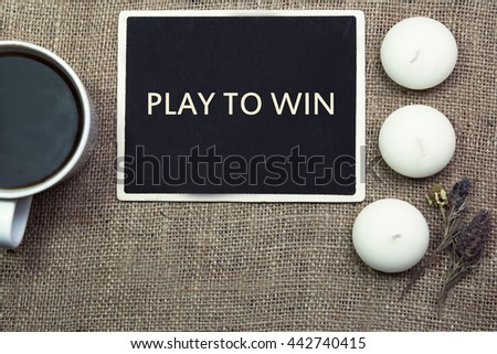 sentence play to win written with chalkboard on a wooden table with pen.coffee white candle.coffee mug.  - stock photo